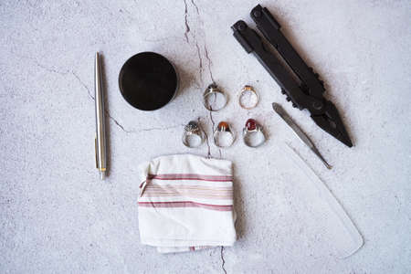 Stylish men's rings, pen, tools, hankerchief, pomade and perfume for grooming. Metrosexual ccessories on concrete background. Urban composition. Top view.