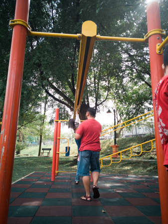 Asian Father and kids playing on monkey bars at the park.