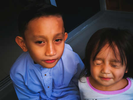 Portrait of asian brother and toddler sister. Family love bonding together concept. Brother is wearing traditional Malay suit.