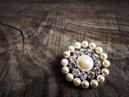 Brooch with white pearl for clothes isolated on wooden background. Brooch with diamond stone. Old precious brooch