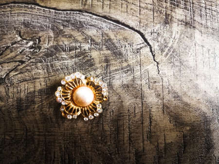 Brooch shaped like flower with big pearl in the middle for clothes isolated on wooden background. Archivio Fotografico