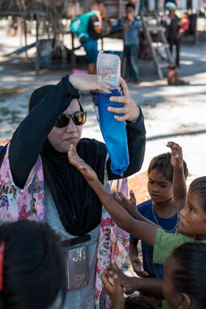 Sibuan, Malaysia - November 26, 2019: Visitors distributing snacks and goods to the Bajau Laut kids in their village.