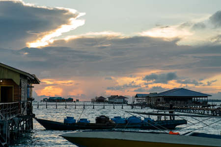 Silhouette of boats and unidentified man working early morning during sunrise in Semporna, Sabah, Malaysia.