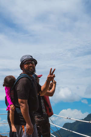 Bearded father with her toddler daughter in ergonomic baby carrier on back outside in mountain nature, show peace sign.