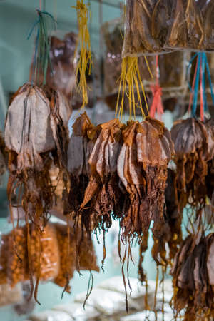 Dried fish tied into several bundles for sale, hanging from above, in a local fish market in Semporna, Sabah.
