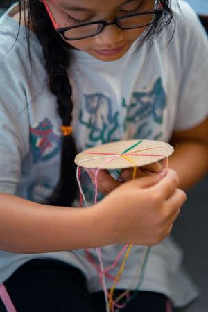 Faire un bracelet d'amitié tressé en utilisant un carton et du fil. Banque d'images