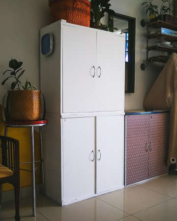 Selangor, Malaysia - December 2019: White living room interior with white cabinet against dark furniture.