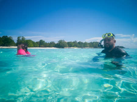 People in snorkeling mask dive underwater with tropical fishes in coral reef sea pool. Travel lifestyle, water sports, outdoor adventure, swimming family summer beach holiday with kids