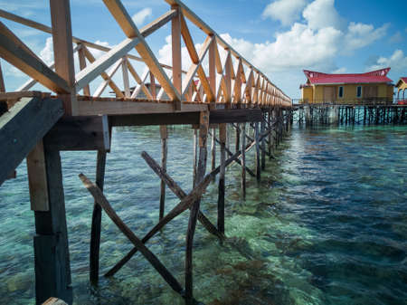 scenery of water chalet above the coral reef during low tide in Semporna island. 免版税图像