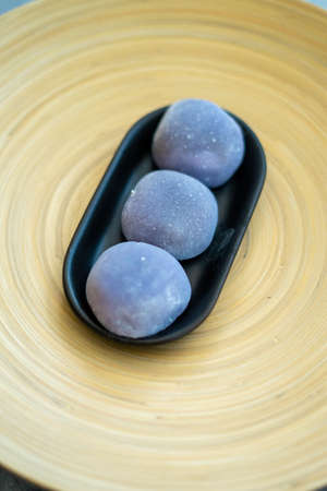 Japanese Mochi in rice dough and on a beautiful bamboo plate and concrete background. Traditional Japanese dessert.