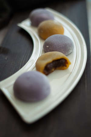 Multi-colored Japanese Mochi in rice dough and on a wooden background. Traditional Japanese dessert.