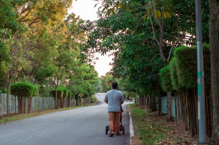 Selangor, Malaysia - January 12, 2019: A father pushing a jogging stroller outside in tropical road enjoying nature.