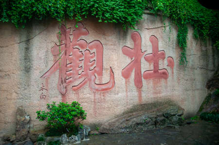 Wuhan, China - April 22, 2019:  Chinese character written in red colour on the wall outdoor.