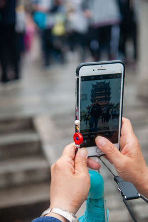 Wuhan, China - Apr 22, 2019 : Tourist taking photo with mobile of the Yellow Crane Tower, the traditional Chinese multi-storey tower located on Sheshan (Snake Hill). Redactioneel
