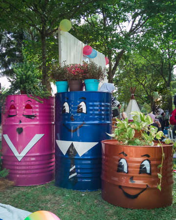 Selangor, Malaysia - Dec 8, 2019 : Oil drum recycled into plant planters and placed in the garden. Cute characters are drawn on it. Stock Photo