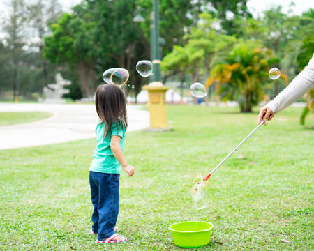 Hermosa niña asiática activa jugando con pompas de jabón al aire libre en el parque