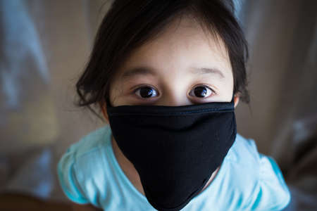 Portrait of asian Little toddler girl wearing reusable black fabric mask for protection from Coronavirus and Covid-19. Copy space.