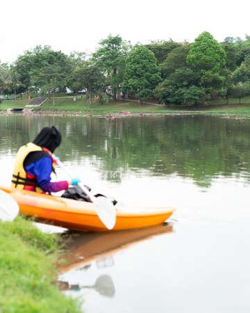 Bangi, Malaysia - Oct 6, 2019: A woman in hijab is kayaking in the Taman Tasik Cempaka lake in the morning.
