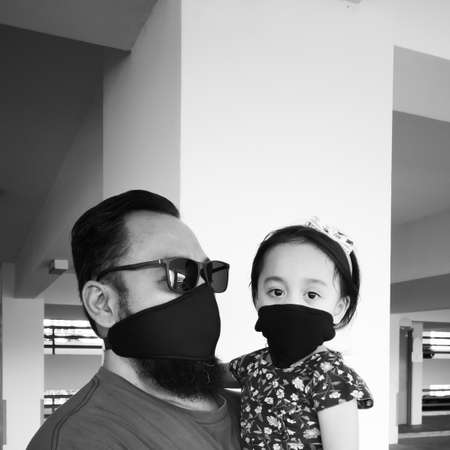 father and toddler girl child wear masks because they are sick or protect themselves from pollution, bacteria or viruses in the air and the environment. Black and white, monochrome.