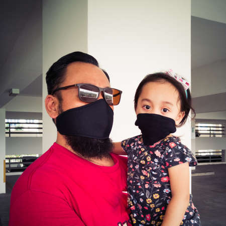 father and toddler girl child wear masks because they are sick or protect themselves from pollution, bacteria or viruses in the air and the environment. 写真素材 - 144860072