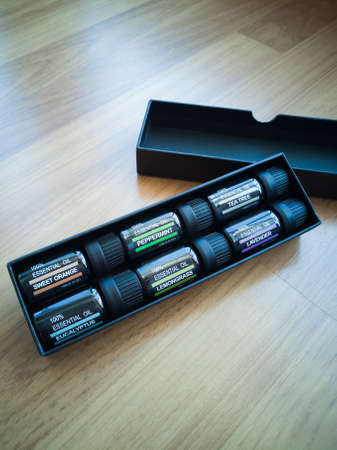 Selection of essential oils, in a black matte box on a wooden background. Gift set. Stock Photo