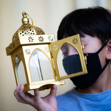 Celebrating Ramadan while wearing medical mask because of corona virus ( Covid-19 ). In the background is a boy with black reusable face mask.