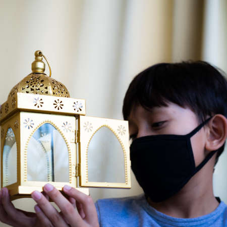 Celebrating Ramadan while wearing medical mask because of corona virus ( Covid-19 ). In the background is a boy with black reusable face mask. Banque d'images