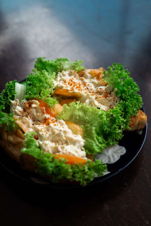 Chicken salad in croissant bun with a healthy salad leaves and tomatoes on a dark, wooden background.