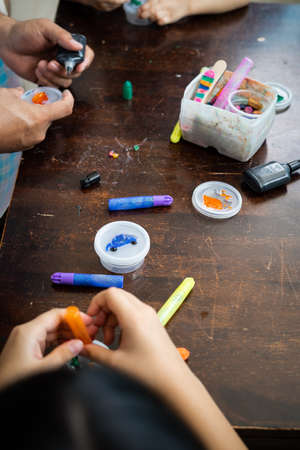 High angle portrait of family painting togeher using glitter glue arts and craft set.