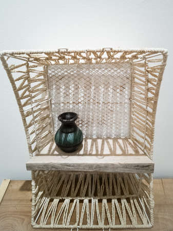 White weaving shelf made from recycled basket and old wooden plank. Upcycling, sustainablity, environmental concept.