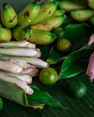 Asian food ingredient lemongrass, calamansi, tumeric leaves and bananas on a banana leaf background.