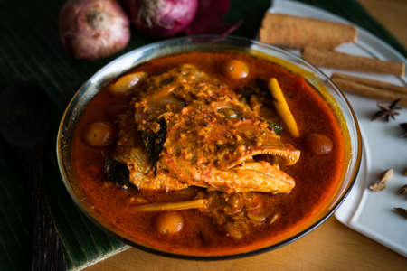 Malaysian traditional dish, fish head curry served on banana leaf with various ingredients spices . Selective focus.