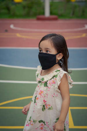 Portrait of toddler wearing reusable black face mask in outdoor.