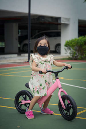 Toddler girl wearing face mask while on a push bike outdoor.
