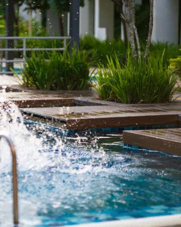 Wooden jumping deck  of swimming pool scene during golden hours with water splash. Standard-Bild