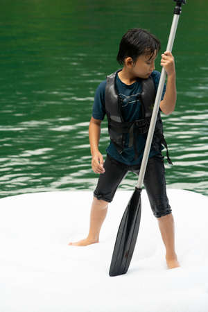 Asian boy wearing life jackets paddling on an inflatable boat in Kenyir Lake, Malaysia.