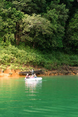 Family wearing life jackets paddling on an inflatable boat in Kenyir Lake, Malaysia.