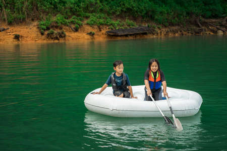 Children wearing life jackets paddling on an inflatable boat in Kenyir Lake, Malaysia. 写真素材