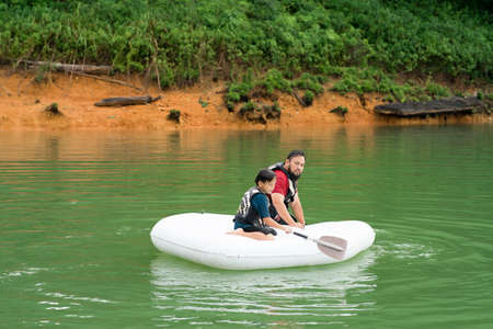 Father and son paddling on an inflatable boat at the Lake Kenyir, Malaysia. 版權商用圖片