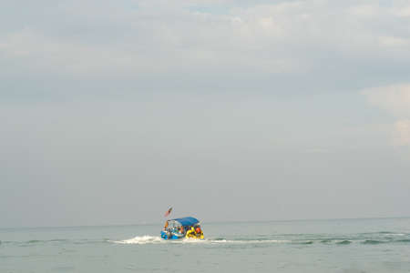Boat with Malaysian flag is pulling children standing on the floating water raft in the sea.
