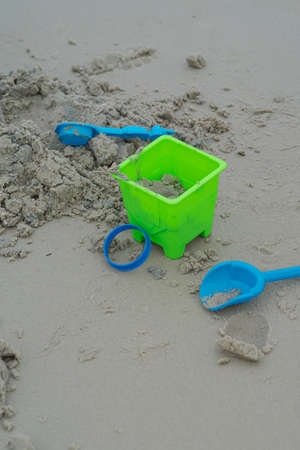 Bright bucket with sand lying by the beach.