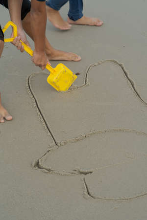 Drawing on sandy surface using yellow shovel by a kid.