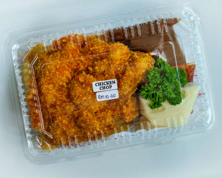 Fried chicken chop, chicken coated in breadcrumbs and fried. Served with black pepper sauce and fries. Take away box. 版權商用圖片
