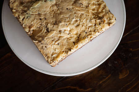 Overhead view of  white  chocolate cake with chocolate rice on a white plate.