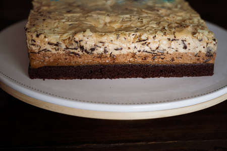 High angle view of  white  chocolate cake with chocolate rice on a white plate.
