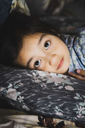Close up toddler asian girl lying in bed with woke up looks. Comfy mattress, soft pillow, fresh bedding, healthy enough sleeping, nap time concept