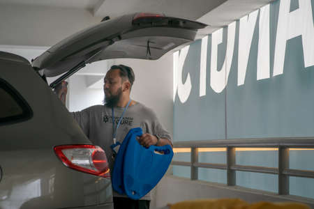 Kuala Lumpur, Malaysia - Sept 26, 2020:  Bearded man packing luggage in a SUV. Joyful man placing travel bags in car getting ready for road trip. Redactioneel