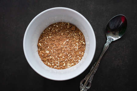 breakfast of healthy banana flakes with chocolate, oat, granola in a white bowl.
