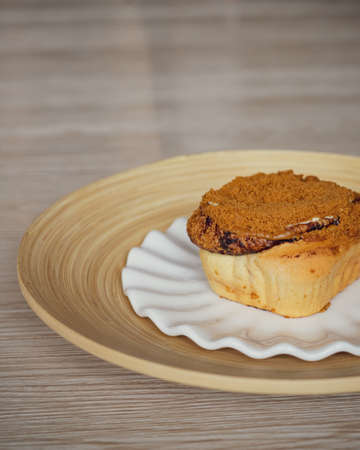 Cinnamon rolls with Lotus BIscoff crumbs topping on a white and bamboo plate.