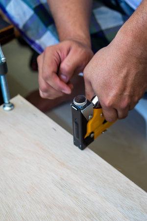 Carpenter using an industrial construction stapler on a wood plank.